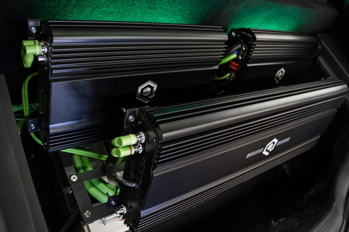 Two SoundQubed Monoblock Amplifiers underneath a SoundQubed Multiple Channel Amplifier, mounted in trunk of a car.