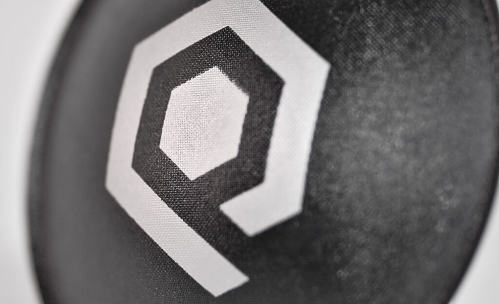 Close up image of a subwoofer dustcap showing detail.